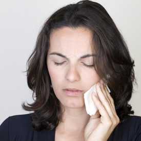 Woman holding cold compress to her cheek