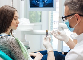 Dentist showing patient dental implant model