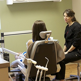 Patient in dental chair talking to team member