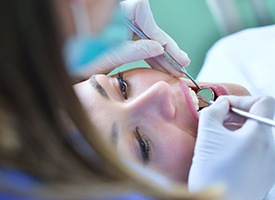 Woman in dental chair receives treatment