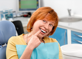Senior woman pointing to teeth