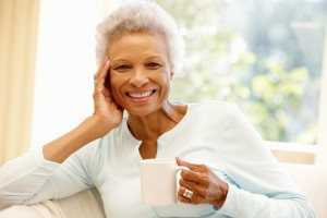 an older lady holding a coffee mug and smiling